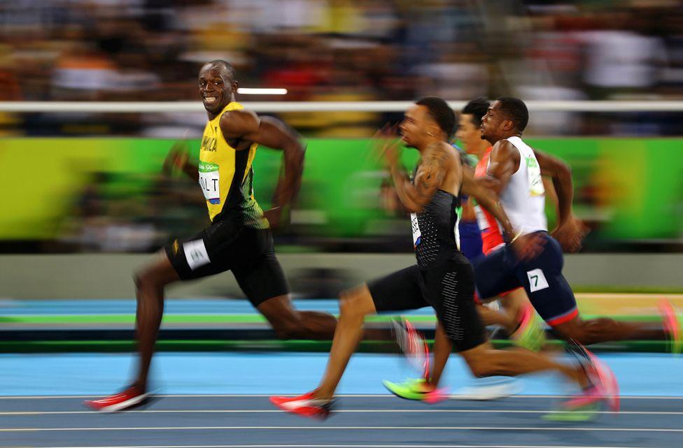 Usain Bolt của Jamaica mỉm cười ngoảnh lại nhìn những đối thủ của mình trong cuộc đua 100 mét vòng bán kết tại Thế vận hội 2016 ở Rio de Janeiro, Brazil