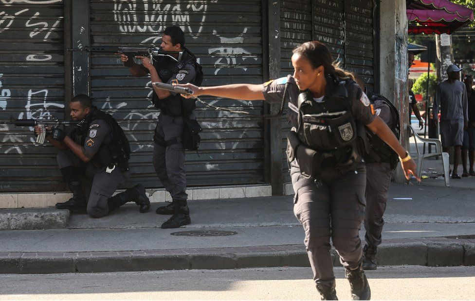 Military Police (PM) officers patrol in the Cidade de Deus'City of God' favela community during an ongoing police operation on 20 November, 2016