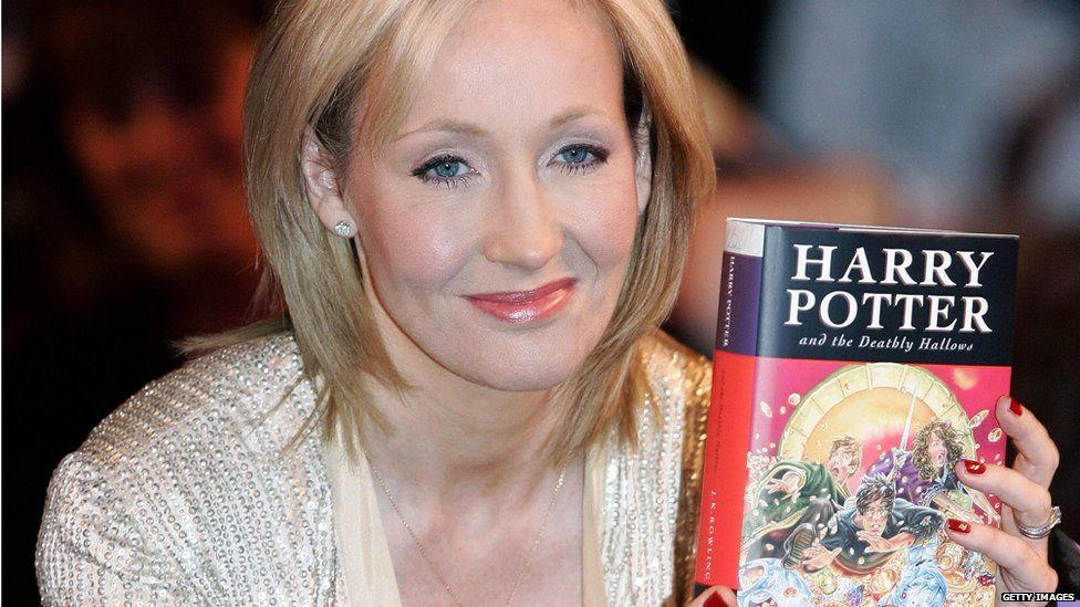 JK Rowling with a copy of The Deathly Hallows