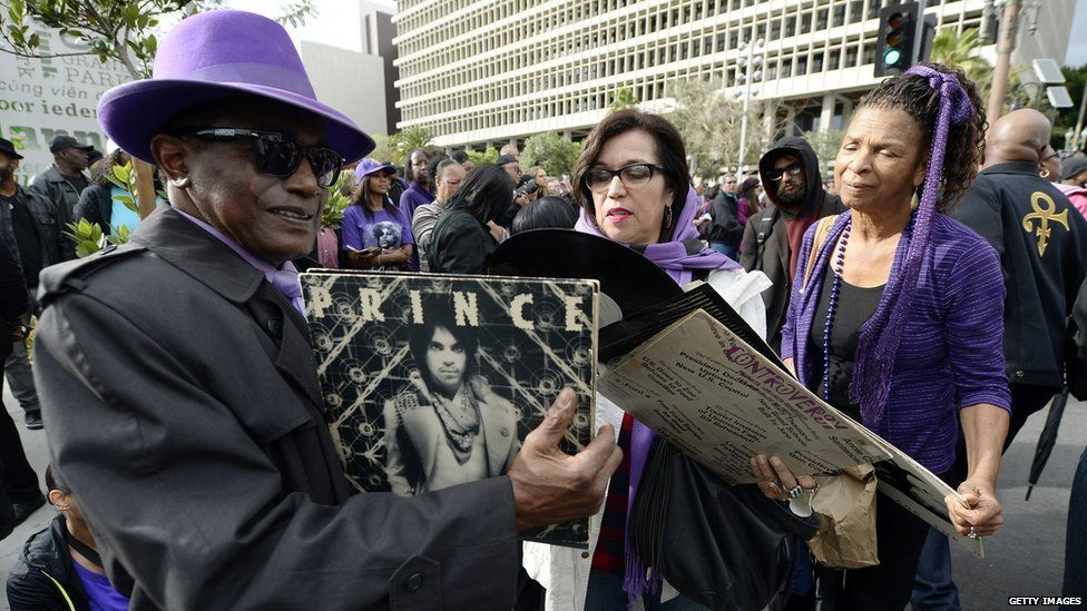 Prince fans hold his records at a memorial