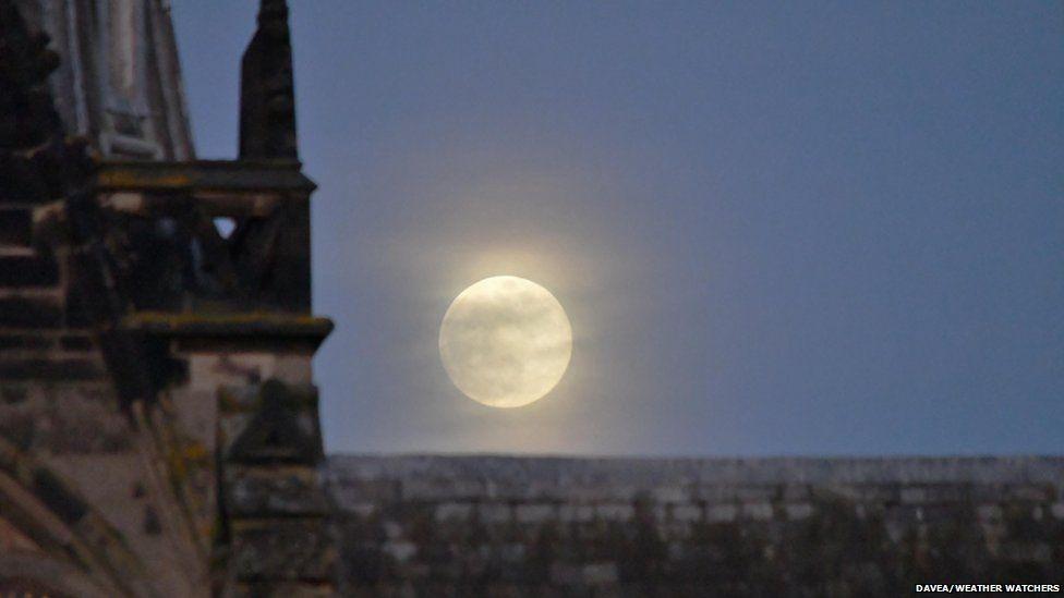 A bright full moon by a church