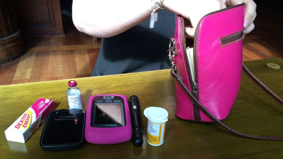 Diabetes medicine and equipment next to a pink handbag