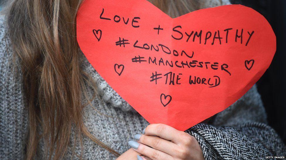 Woman holds Manchester/London heart
