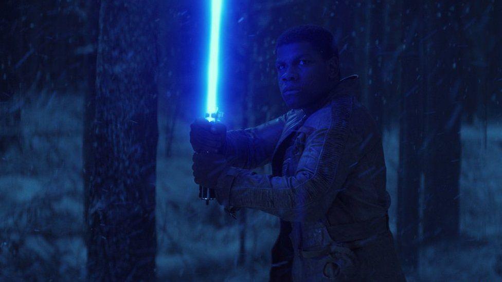 Finn, played by John Boyega weilds a lightsaber