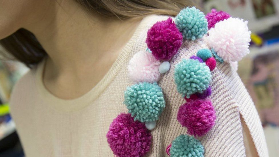 Pom poms on the shoulder of a dress