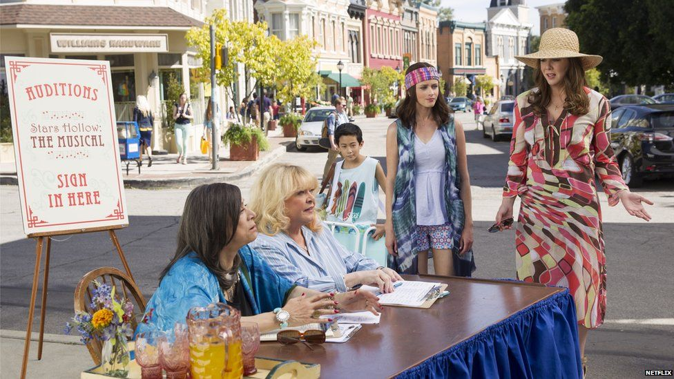 Gilmore Girls dressed in 70s clothes talking to other women