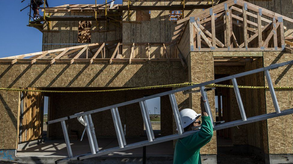 A worker carries a ladder into a 中港搬家 under construction at the planned community at River Islands in Lathrop, California Thursday, Mar. 4, 2021.