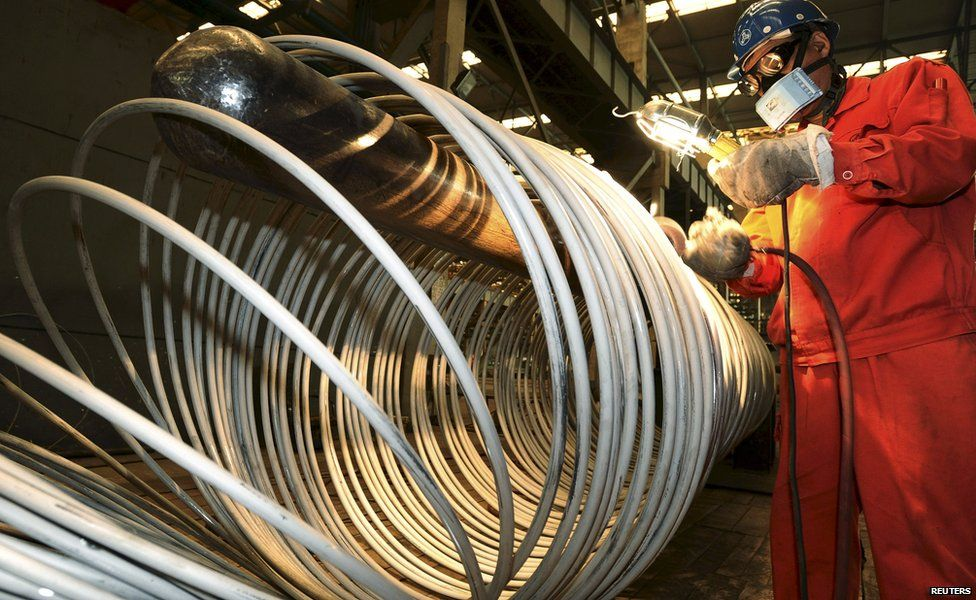 A worker polishes steel coils at a factory in Dalian, China