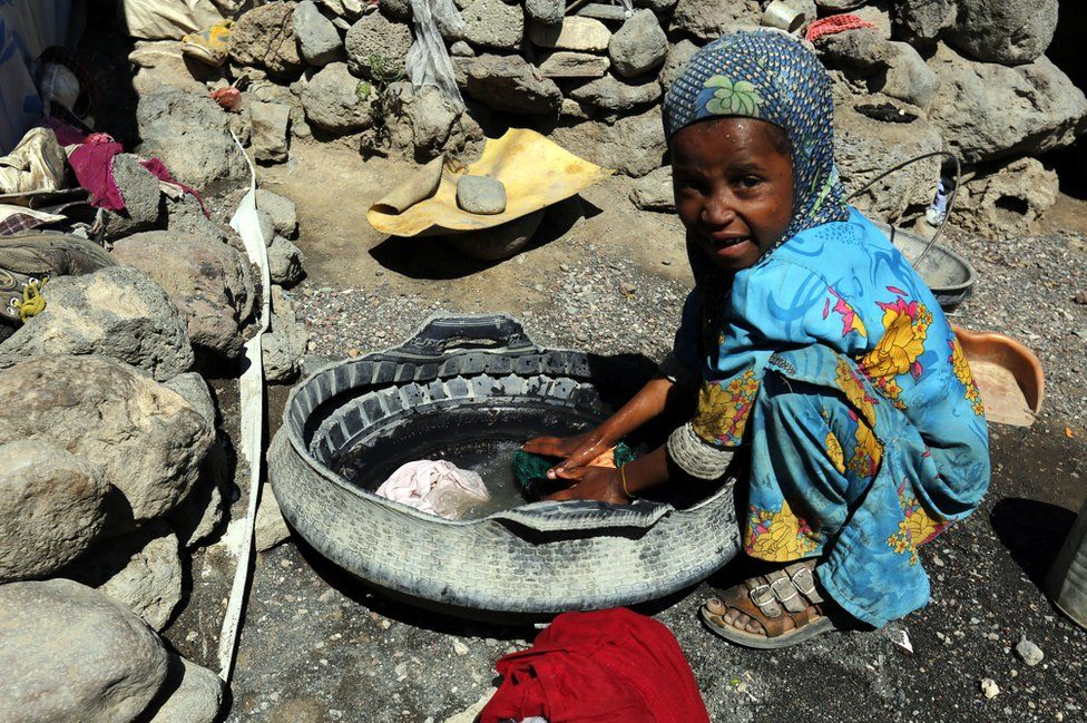 A small girl washes clothing in a makeshift container