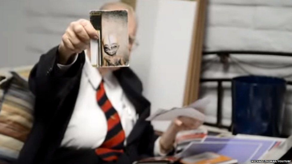 Boyd Bushman holds up a photo of an alien being