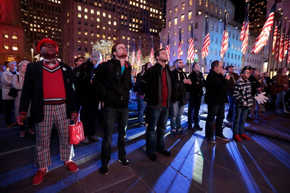 A crowd watches a news report at Rockefeller Center