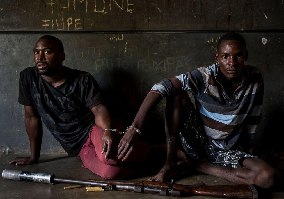Hai người săn trộm tê giác, một 19 tuổi, một 28 tuổi, đang đợi làm thủ tục ở một nhà tù địa phương ở Mozambique, gần biên giới khu Bảo tồn Quốc gia Kruger.
