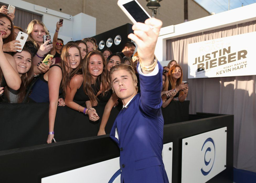 Justin Bieber taking a selfie with fans
