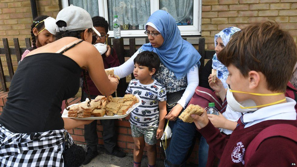 Woman handing out sandwiches to residents