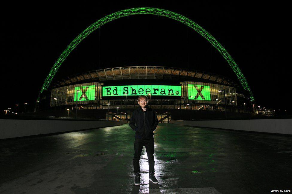 Ed Sheeran standing outside Wembley Stadium