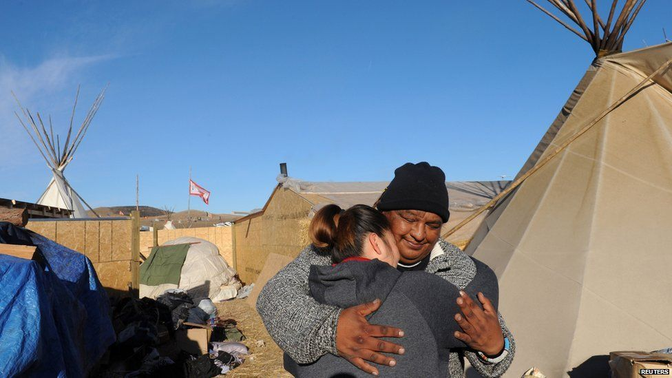 This is a photo of people two native American people on the Sioux reservation site.
