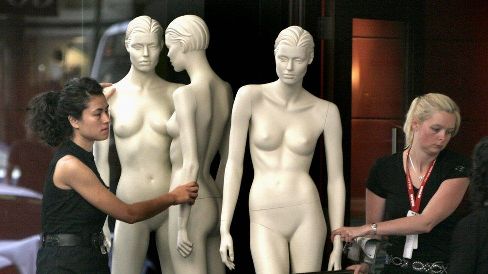Women moving shop mannequins