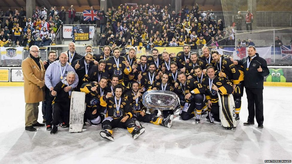 This is a photo of the Nottingham Panthers team posing with their winning medals and trophies.