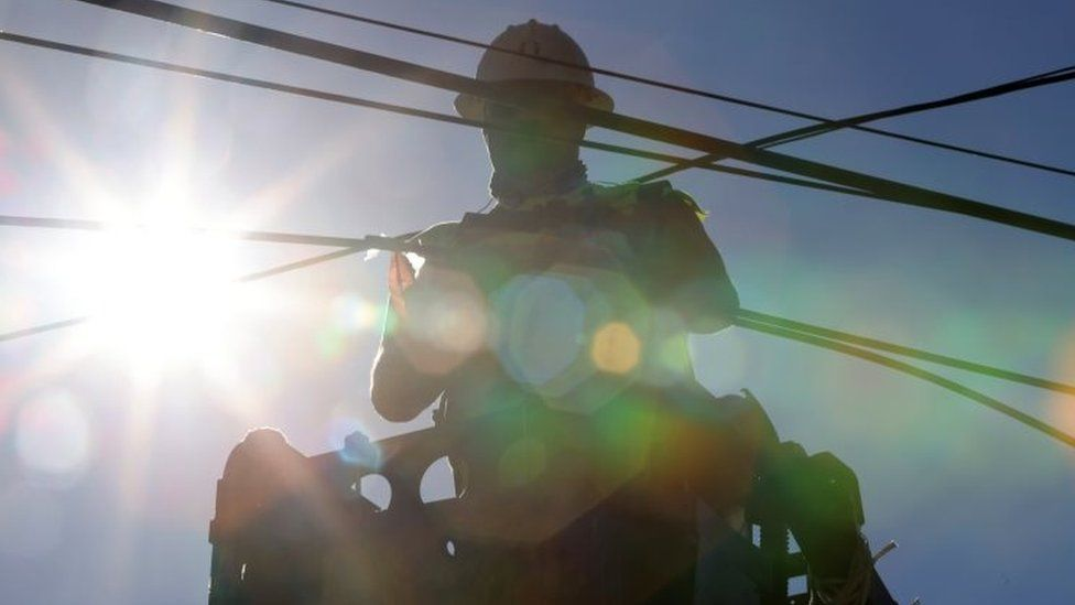 A worker tends to a fibre-optic line in Lake Forest Park, Washington, amid the scorching heat