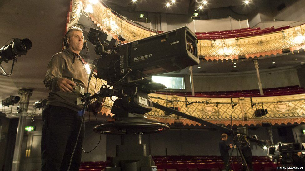A camera operator filming for NT Live