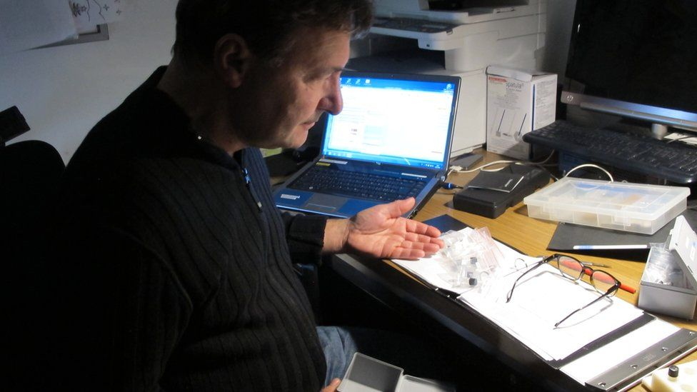 A man with drug samples on a desk