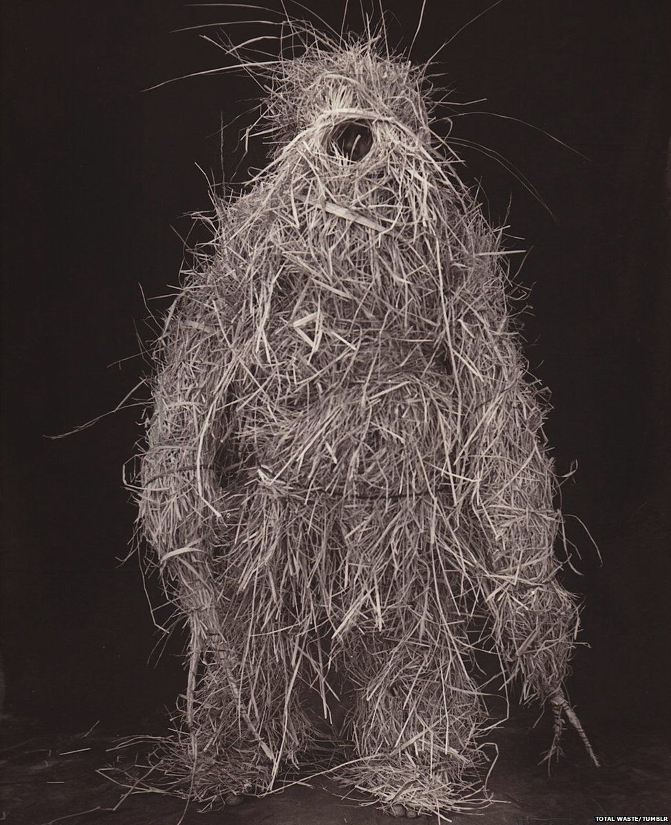 A person covered in straw
