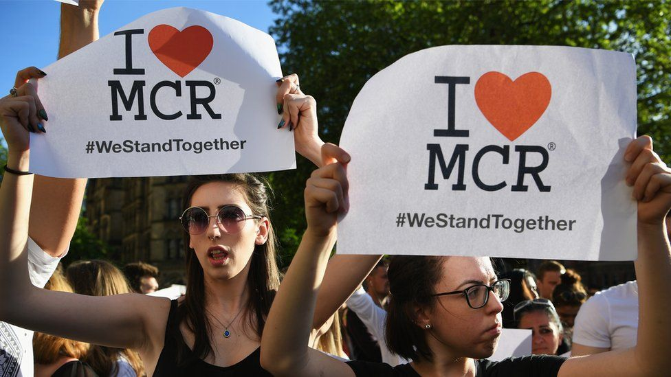 People holding we love manchester signs