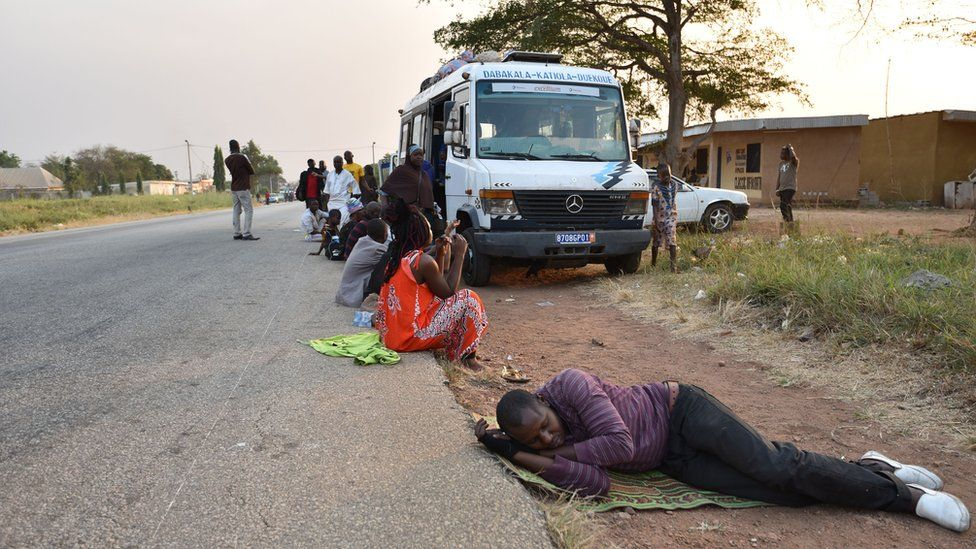 Passengers in Ivory Coast rest next to a bus, some 15km from Bouake which was rocked by a mutiny
