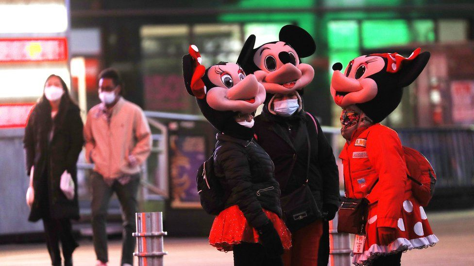 people wearing Minnie Mouse and Mickey Mouse costumes engage in conversation in Times Square on March 15, 2021 in New York City. After undergoing various shutdown orders for the past 12 months the city is currently in phase 4 of it's reopening plan, allowing for the reopening of low-risk outdoor activities, movie and television productions, indoor dining as well as the opening of movie theaters, all with capacity restrictions. (