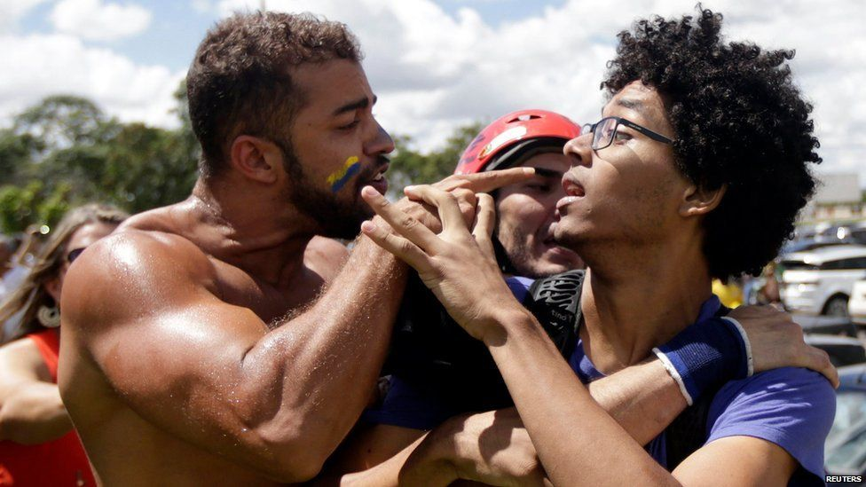 An anti-government demonstrator (L) and a supporter of Brazil's President Dilma Rousseff clash before the appointment of former Brazilian president Luiz Inacio Lula da Silva as chief of staff, near the Planalto palace in Brasilia, Brazil, March 17, 2016.
