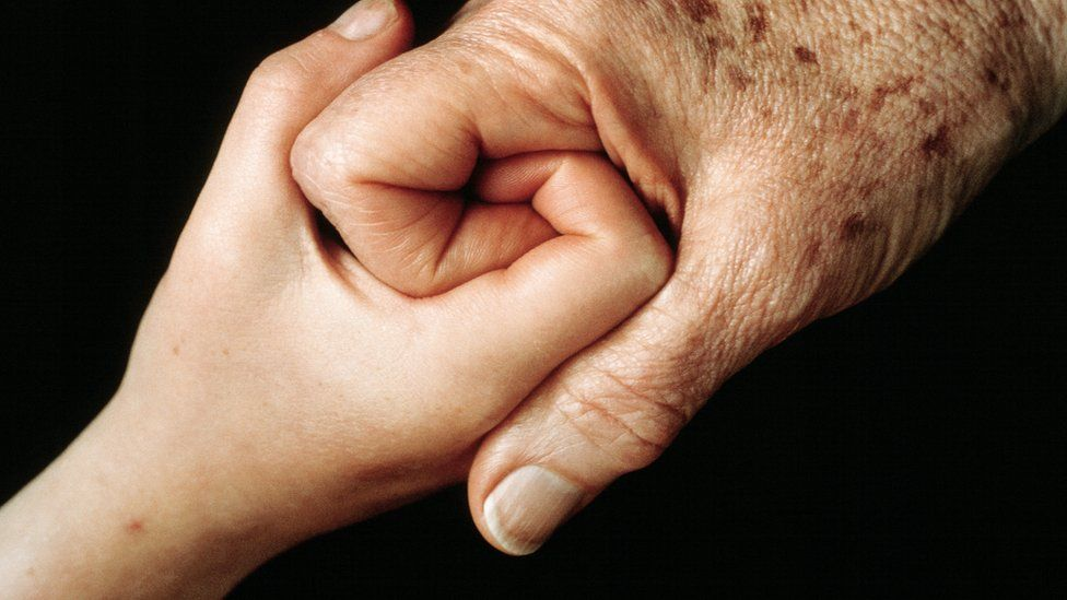 A young hand clasping and older hand