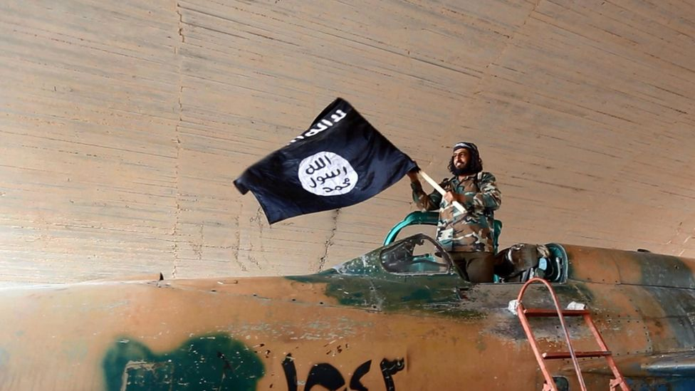 Islamic State fighter (ISIS; ISIL) waving a flag while standing on captured government fighter jet in Raqqa, Syria 2015