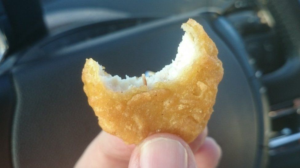 Picture of a half-eaten McDonald's chicken nugget with what looks like a small worm inside