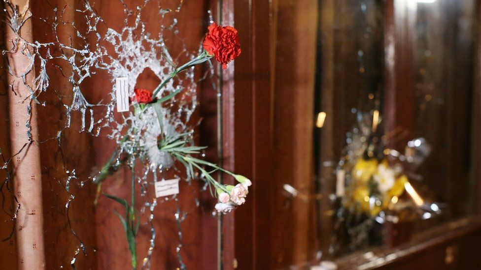 Flowers pushed through bullet holes in glass