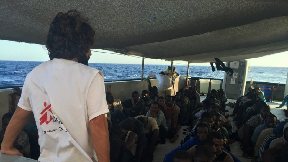A Médecins Sans Frontières worker looks on at a group of rescued refugees
