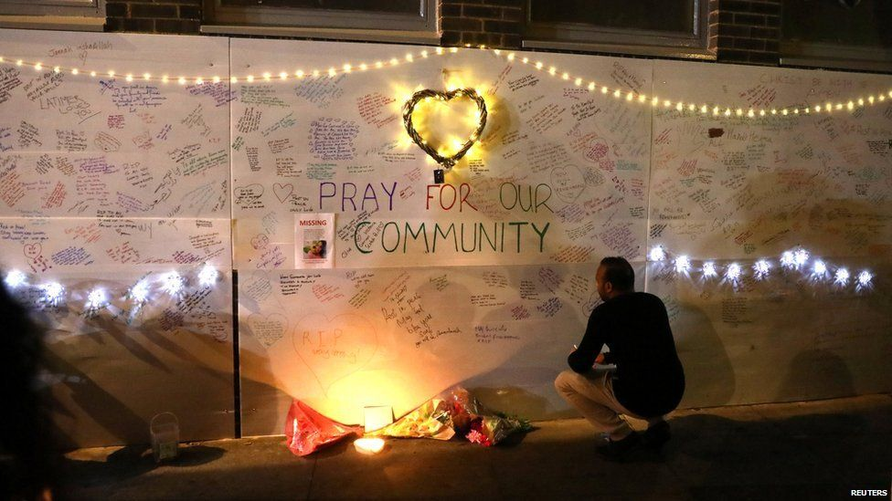 messages of condolence on a wall near a tower block