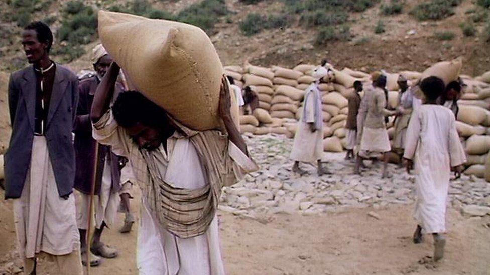 Men carrying sacks