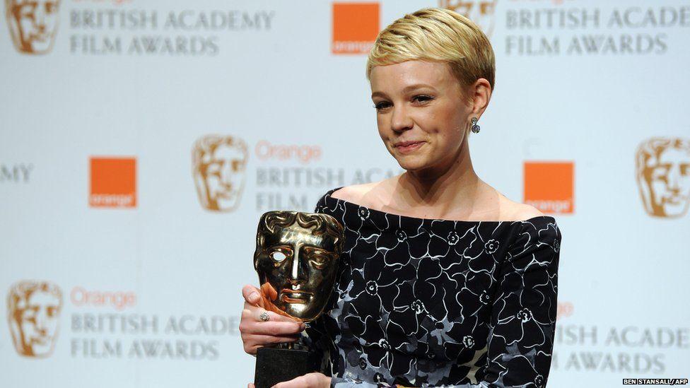 Carey Mulligan holding her BAFTA award