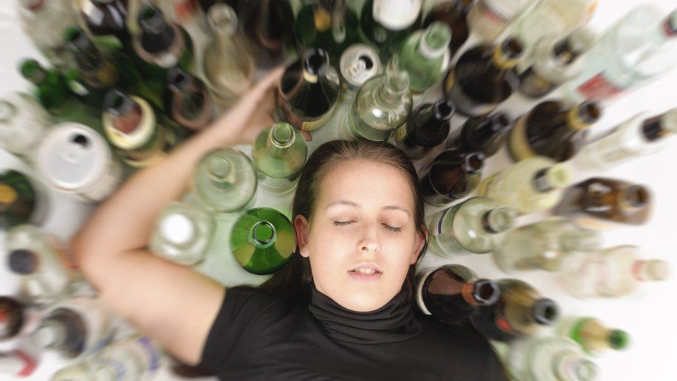 A woman lying down surrounded by empty bottles