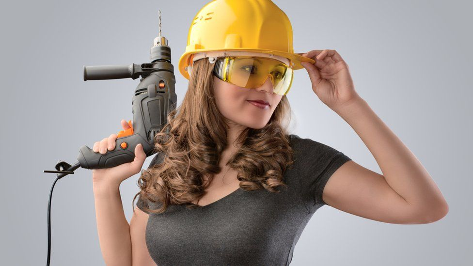 Glamorous woman with a hard hat and drill