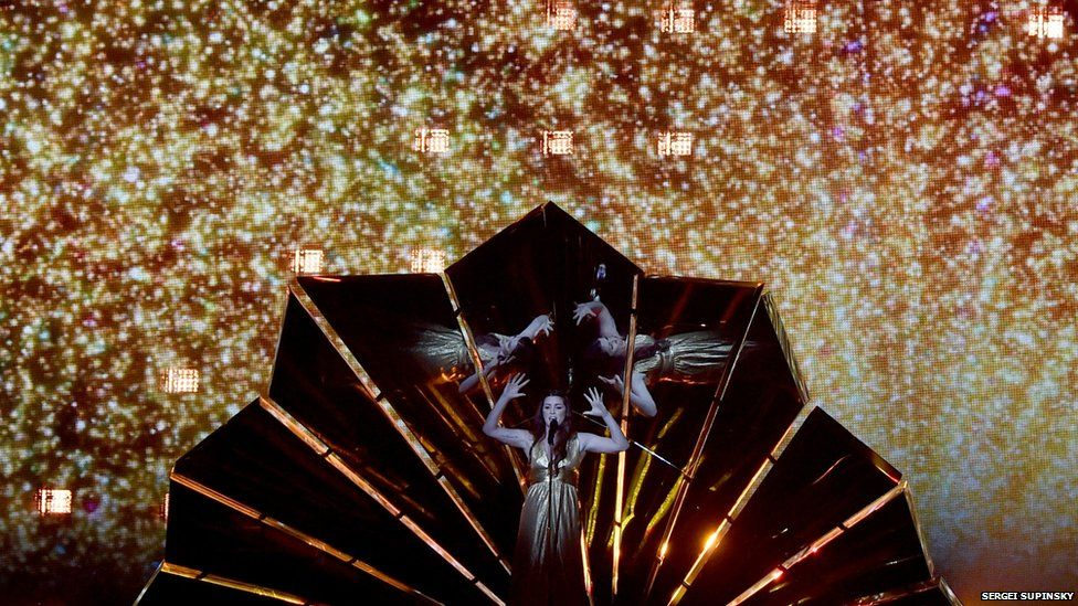 Lucie is performing inside a giant mirrored shell in front of a CGI display of stars