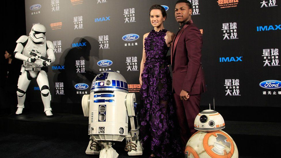 Daisy Ridley and John Boyega at a premiere with R2D2, BB8 and a storm trooper