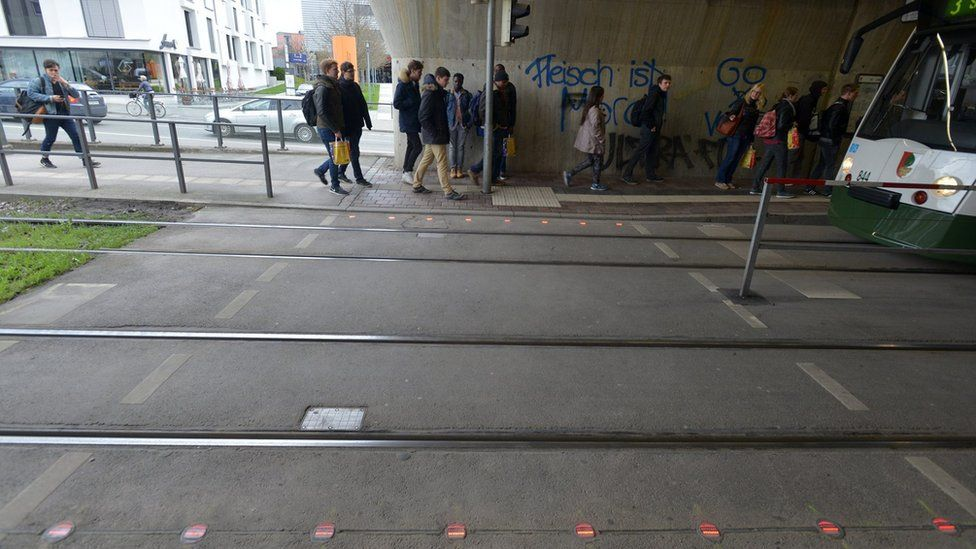Traffic crossing with red lights in the pavement