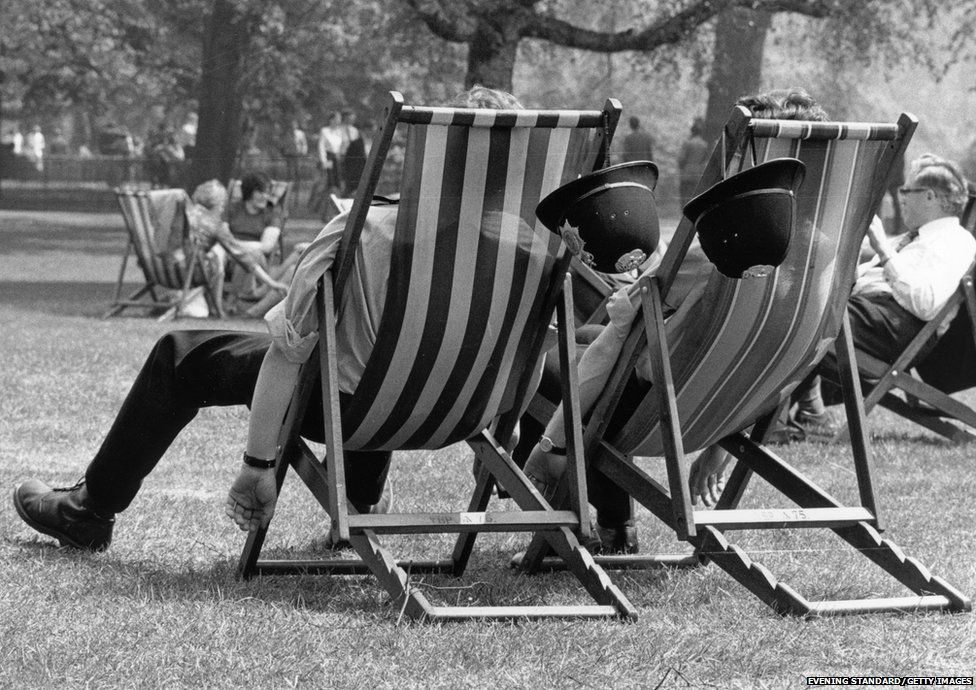 Two London policemen take the weight off their feet during the May heatwave, while patrolling in the park