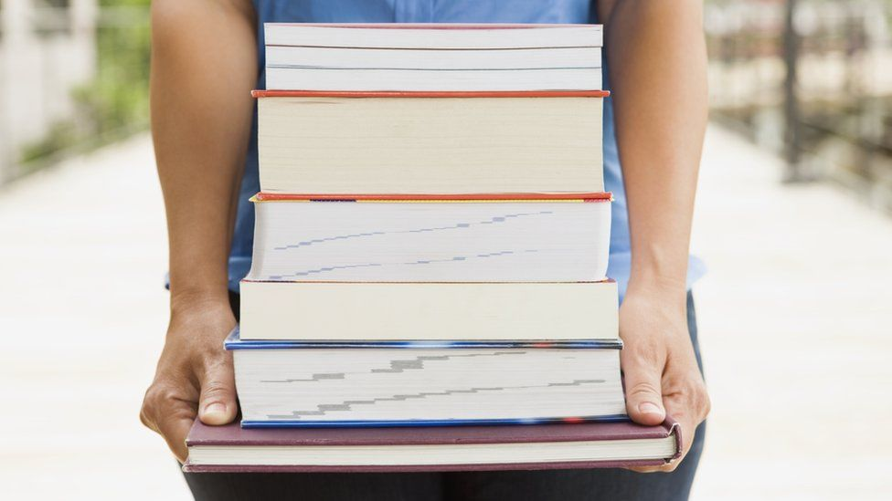 Person carrying a stack of books