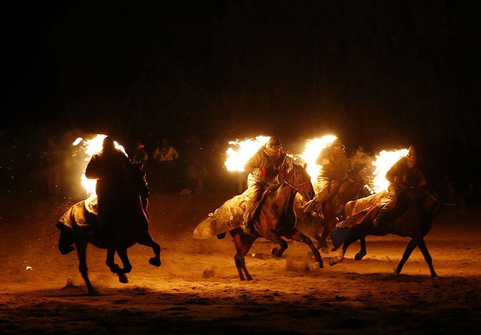 Tres jinetes rodeados de llamas en los Juegos Nómadas Mundiales en Kirguistán