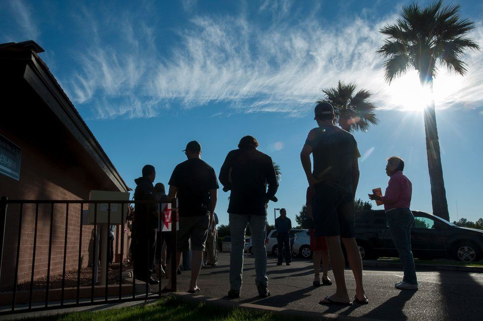 Voters wait in line in front of a polling station to cast their ballots in the US presidential election in Scottsdale, Arizona