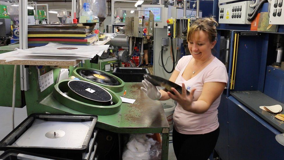 A worker inspects a vinyl record at a factory in the Czech Republic