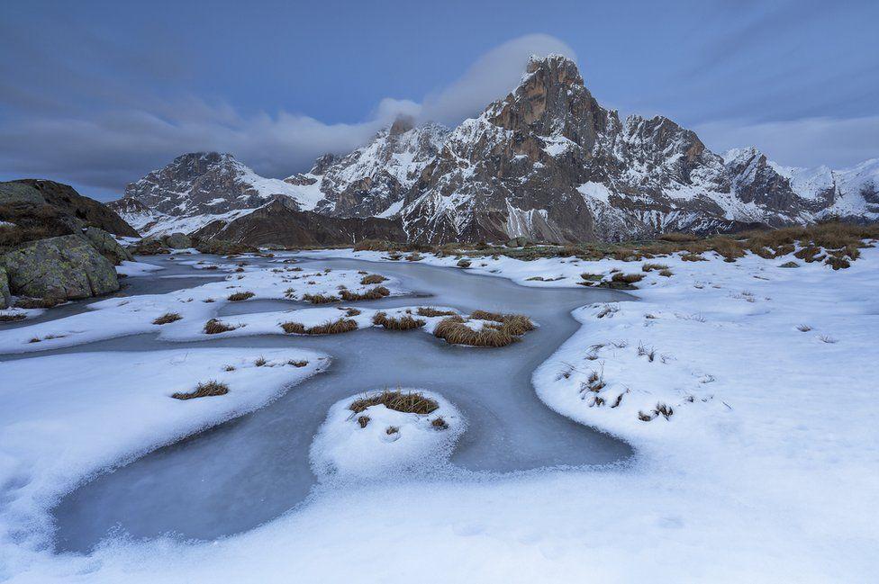 Estanque congelado con las montañas de fondo