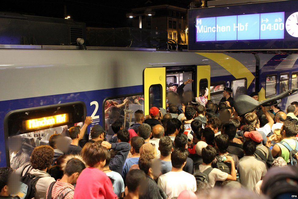 Migrants try to board a train in Budapest